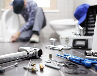 a Home Climates technician fixing a plumbing problem in a Harrisburg house
