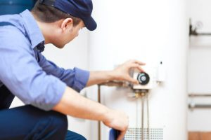 a home climates employee serving a water heater in Lancaster Pennsylvania