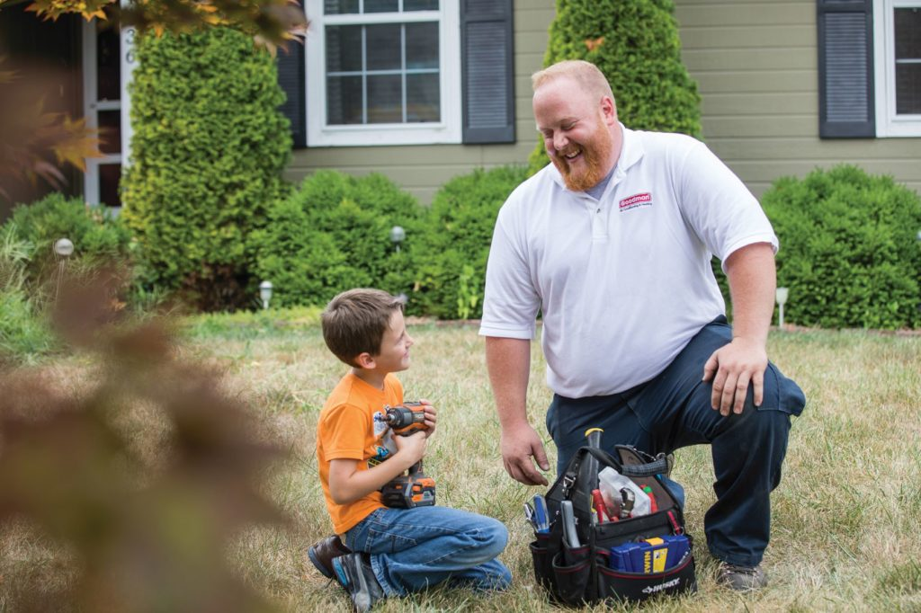 HVAC technician kneeling down in a yard with his tool kit to talk to a child.
