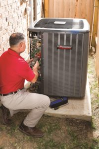 Home Climates technician repairing an AC system.